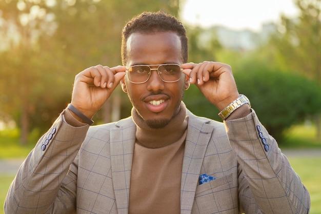Porträt eines jungen und gutaussehenden, stilvollen afroamerikanischen mannes in einer stilvollen braunen anzugarmbanduhr setzt eine brille in einem sommerpark auf. latino hispanischer geschäftsmann schwarzer kerl posiert beim fotoshooting.