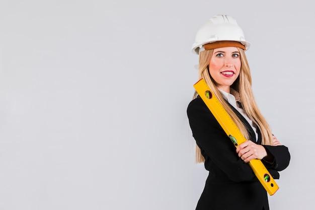 Porträt eines jungen weiblichen architekten, der in der hand das machthaber betrachtet kamera hält