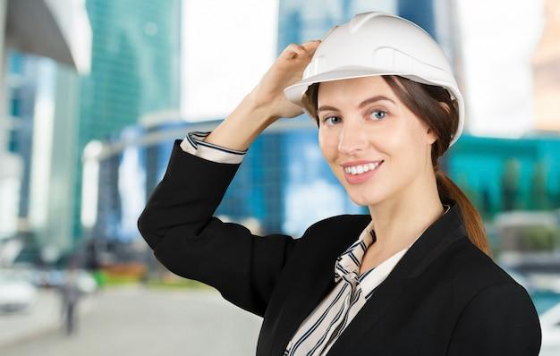 Porträt eines jungen weiblichen ingenieurs, der einen schutzhelm trägt