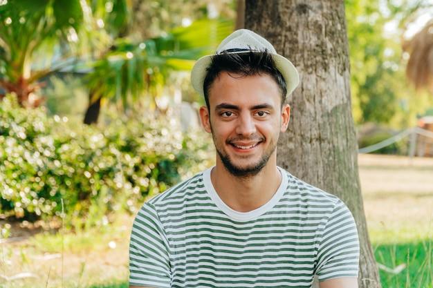 Porträt eines jungen weißen mannes, der einen hut trägt und in einem park lächelt.