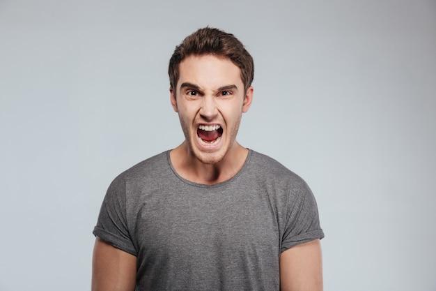 Porträt eines jungen wütenden mannes, der über weiß schreit und in die kamera schaut