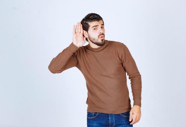 Porträt eines jungen zufälligen mannes, der das gespräch belauscht