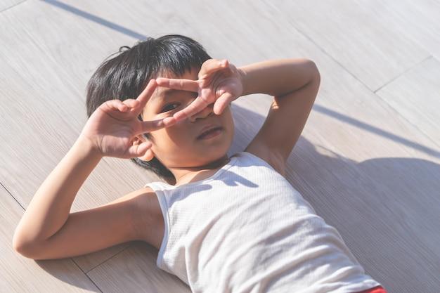 Porträt eines jungenauges, das durch seine hand schaut