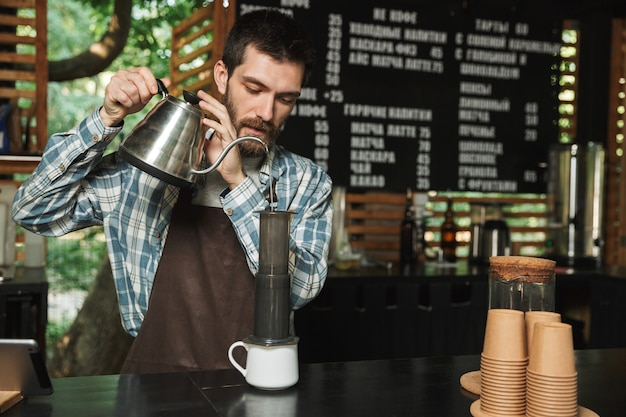 Porträt eines kaukasischen barista-mannes mit schürze, der kaffee macht, während er im straßencafé oder kaffeehaus im freien arbeitet?