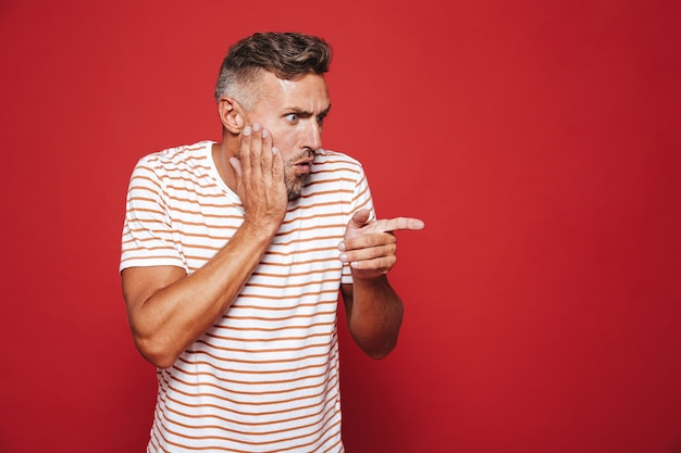 Porträt eines kaukasischen erwachsenen mannes, der sein gesicht greift und mit dem finger auf das exemplar isoliert auf rot zeigt