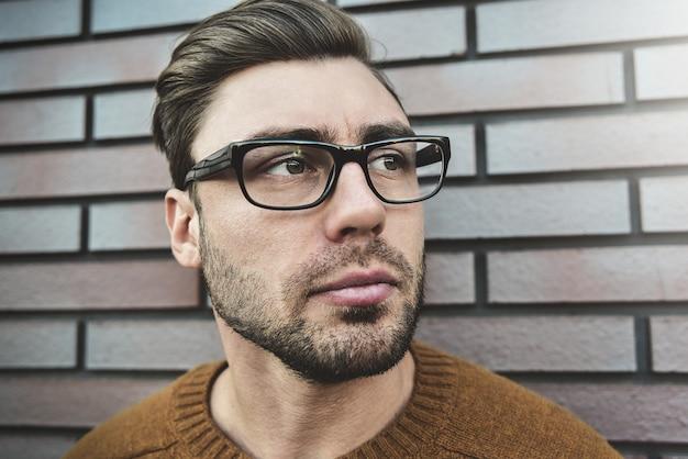 Porträt eines kaukasischen gutaussehenden mannes in der brille, die ernsthaft die stirn runzelt. emotionales gesichtskonzept.