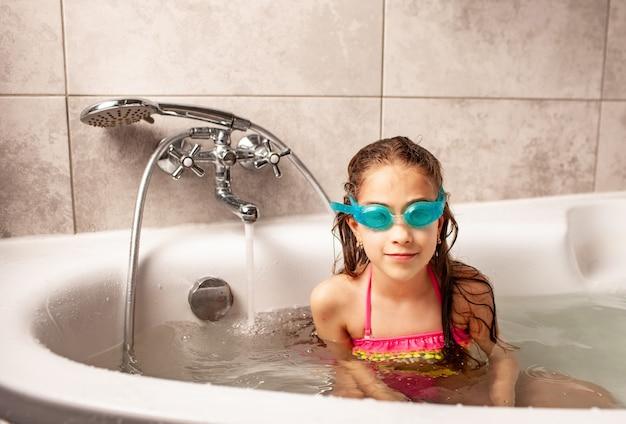 Porträt eines kaukasischen lustigen kleinen mädchens in einem badeanzug und einer schwimmbrille
