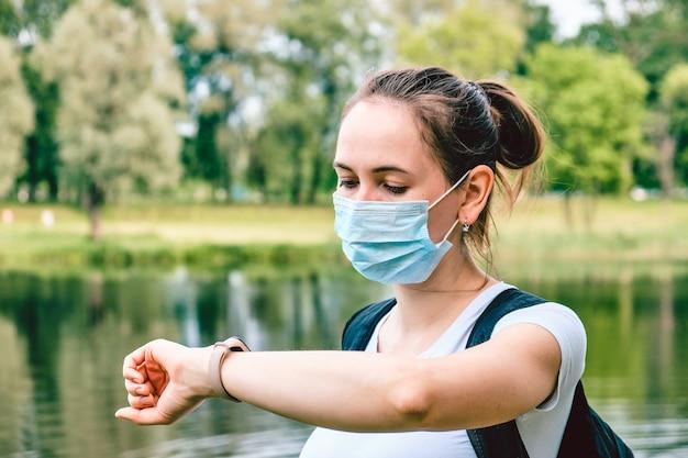 Porträt eines kaukasischen mädchens in einer medizinischen maske und schaut auf eine intelligente uhr. neue normalität und neues leben während einer pandemie.
