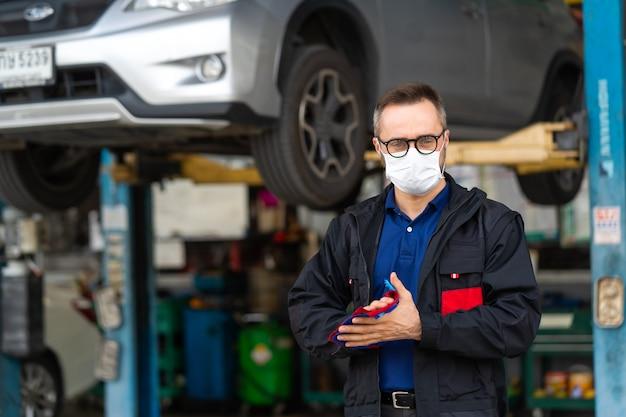 Porträt eines kaukasischen mannes, der hände mit tuch säubert und medizinische gesichtsmaskenschutz-coronavirus trägt. fachkundiger mechaniker, der in der autowerkstatt arbeitet.