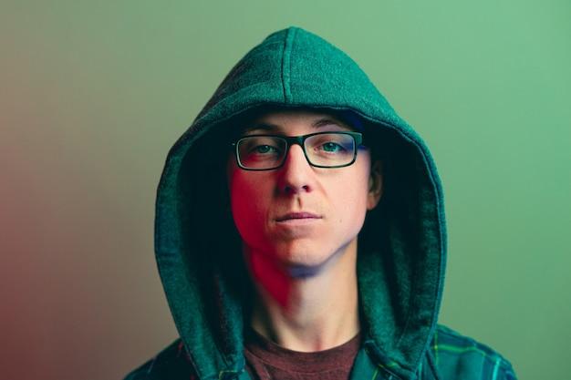 Porträt eines kaukasischen mannes mit einem pokergesicht, das eine brille und einen kapuzenpulli mit grünem lichteffekt trägt