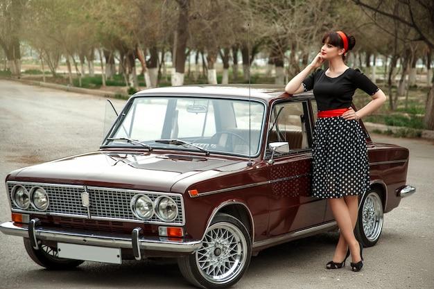 Porträt eines kaukasischen schönen jungen mädchens in einem schwarzen weinlesekleid, werfend nahe einem weinleseauto auf