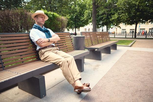 Porträt eines kerls, der auf einer parkbank sitzt