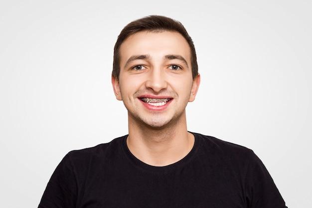 Porträt eines kerls in einem schwarzen t-shirt in den klammern