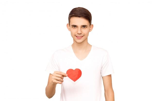 Porträt eines kerls in einem weißen t-shirt, das ein herz, isolat hält