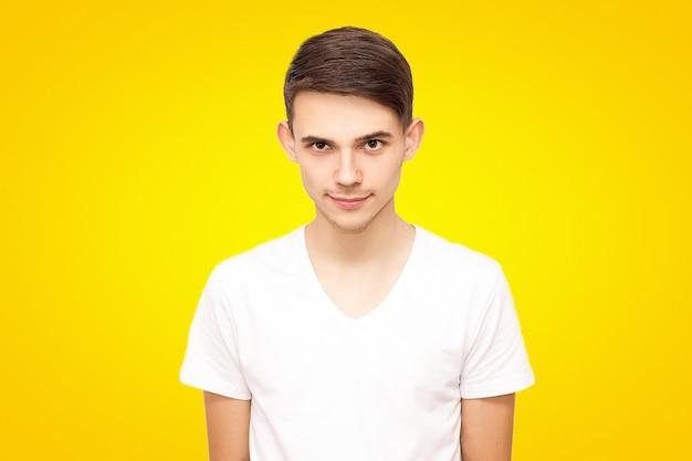Porträt eines kerls in einem weißen t-shirt, lokalisiert auf einem gelben hintergrund