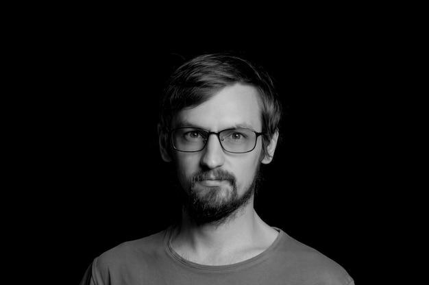 Porträt eines kerls mit einem bart in den gläsern auf einem schwarzen hintergrund