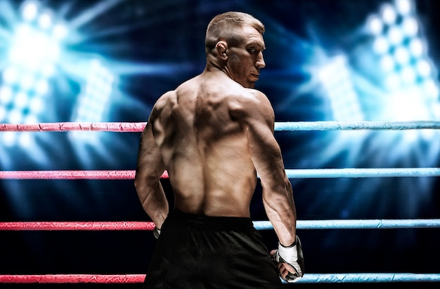 Porträt eines kickboxers auf dem hintergrund heller scheinwerfer. rückansicht. das konzept von sport und mixed martial arts. gemischte medien