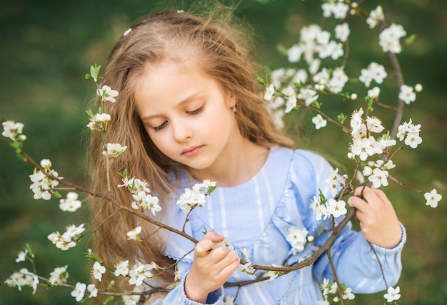 Porträt eines kindermädchens in einem blühenden garten. frühlingsfoto. blumen in deinen haaren