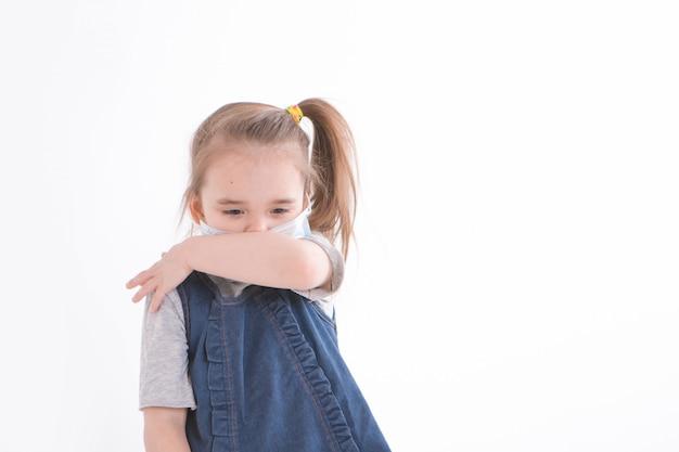 Porträt eines kindes auf einem weißen, der eine medizinische maske trägt.