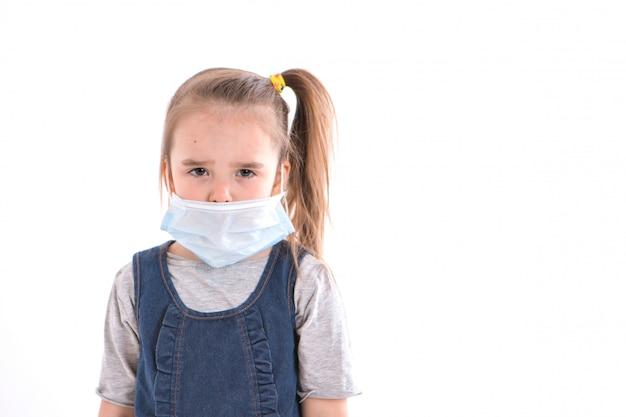 Porträt eines kindes auf einem weißen hintergrund, der eine medizinische maske trägt.