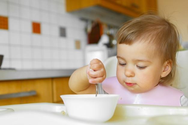 Porträt eines kindes, das babynahrung mit seinem löffel isst. mein gesicht ist mit essen verschmiert