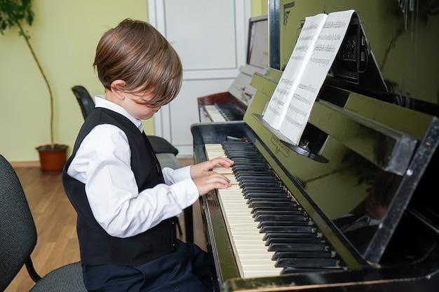 Porträt eines kindes, das klavier spielt, junge, der musik mit einem klavier in der musikschule lernt. kind entspannt klavier spielen