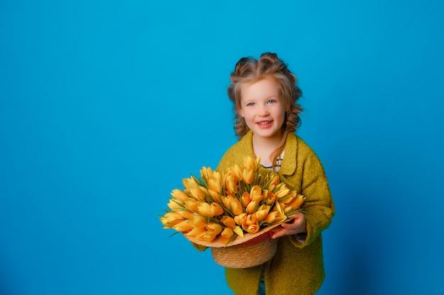 Porträt eines kindes ein mädchen im regen stiefel ein strauß frühlingsblumen tulpen auf einem farbigen blauen raum