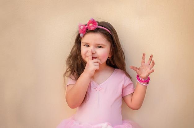 Porträt eines kindes in einem kleid. mädchen auf einem hellen hintergrund in einem rosa kleid isst schokolade