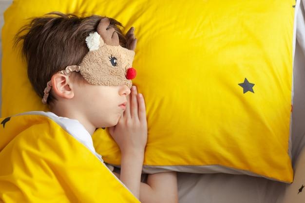 Porträt eines kindes in einer schlafmaske, die an einem morgen im gelben bett schläft.