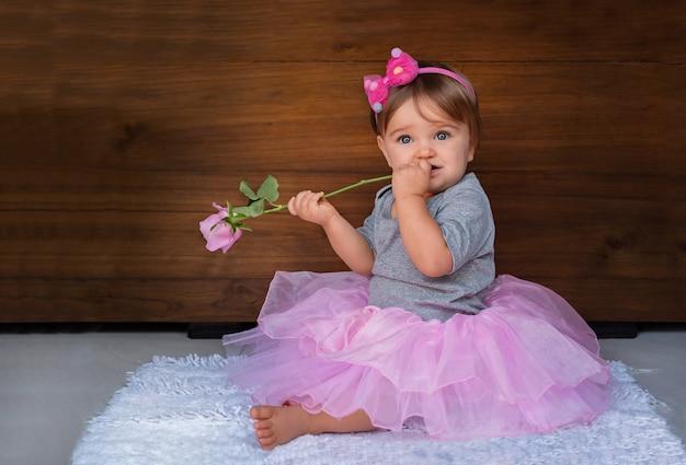 Porträt eines kindes mit einer rose auf einem hölzernen hintergrund. baby in rosa schmuck mit einer rosa blume auf einem hölzernen hintergrund.