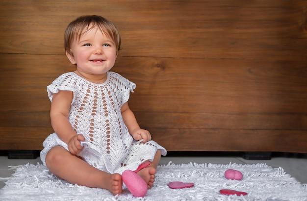 Porträt eines kindes mit herzen auf einem hölzernen hintergrund. baby in einem weißen kleid mit rosa herzen auf einem hölzernen hintergrund.