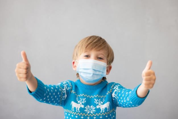 Porträt eines kindes mit medizinischer maske weihnachtsferien während der pandemie des coronavirus covid19
