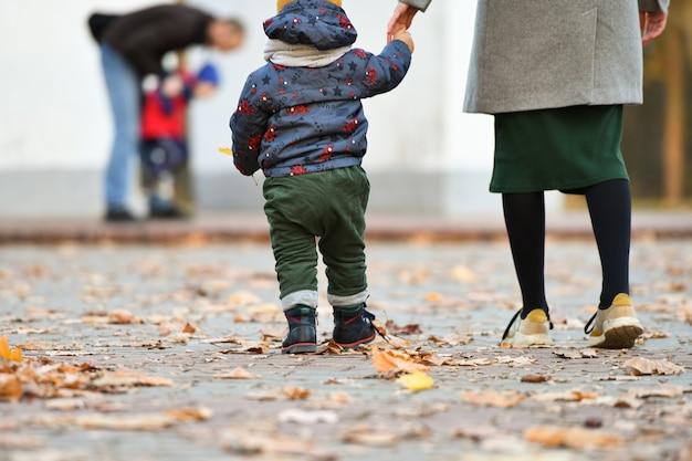 Porträt eines kindes mit mutter, die auf gelbem laub geht.