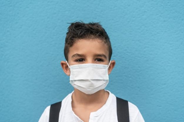 Porträt eines kindes mit sicherheitsmaske, das zur schule geht - fokus auf gesichtsmaske