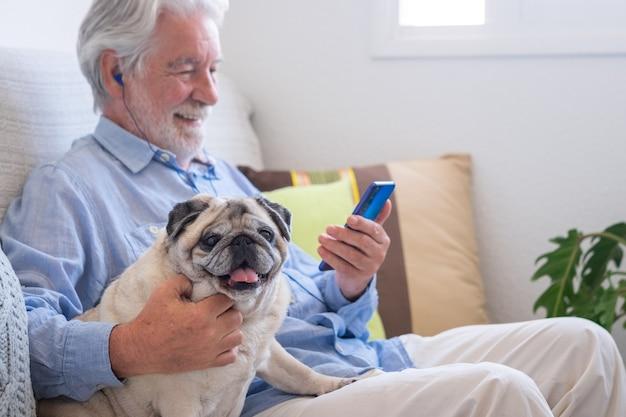 Porträt eines klaren reinrassigen mopshundes, der mit seinem seniorbesitzer auf dem sofa sitzt und sich zu hause zusammen entspannt