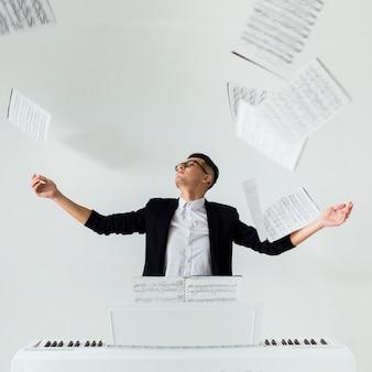 Porträt eines klavierspielers, der die musikalischen blätter in der luft sitzt vor dem weißen hintergrund wirft