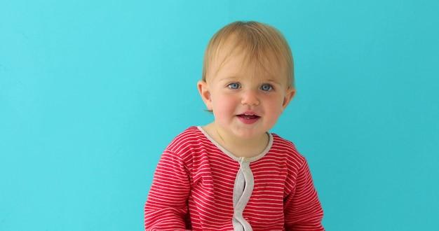 Porträt eines kleinen 11-monatigen alten mädchens, das kamera auf einem blauen hintergrund lächelt und betrachtet