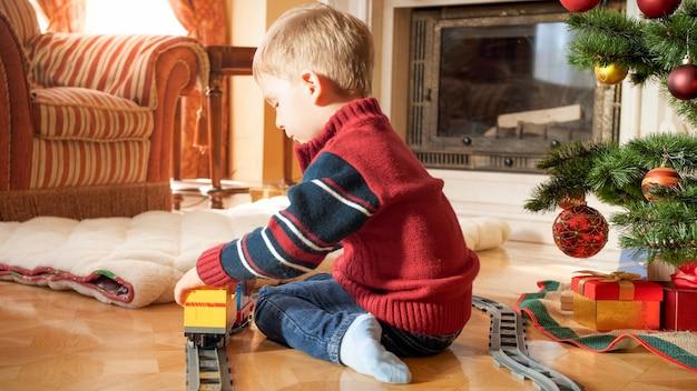 Porträt eines kleinen 3-jährigen jungen, der neben dem weihnachtsbaum sitzt und mit spielzeugeisenbahn spielt. kind, das an neujahr oder weihnachten geschenke und spielzeug erhält
