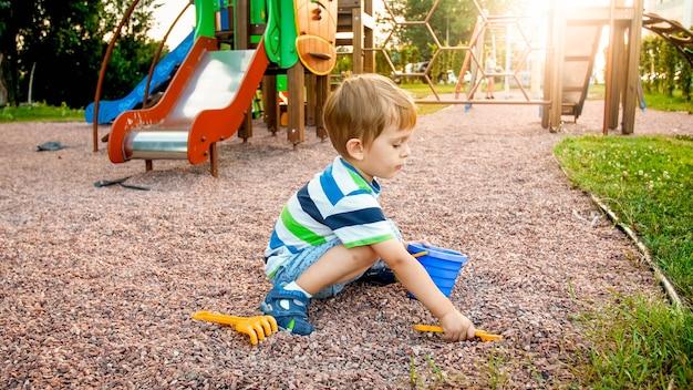 Porträt eines kleinen 3 jahre alten kleinkindjungen, der auf dem spielplatz sitzt und sand mit spielzeugplastikschaufel gräbt