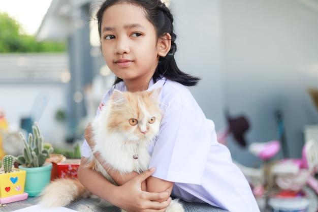 Porträt eines kleinen asiatischen mädchens in thailändischer studentenuniform umarmt ihre persische katze mit glück, wählen sie fokus flache schärfentiefe