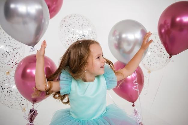 Porträt eines kleinen blonden mädchens, das mit luftballons auf weißem hintergrund mit einem platz für text spielt