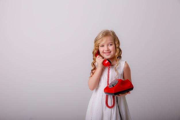 Porträt eines kleinen blonden mädchens mit einem alten telefon in ihren händen