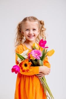 Porträt eines kleinen blonden mädchens mit einem blumenstrauß der frühlingsblumen auf einer hellen wand