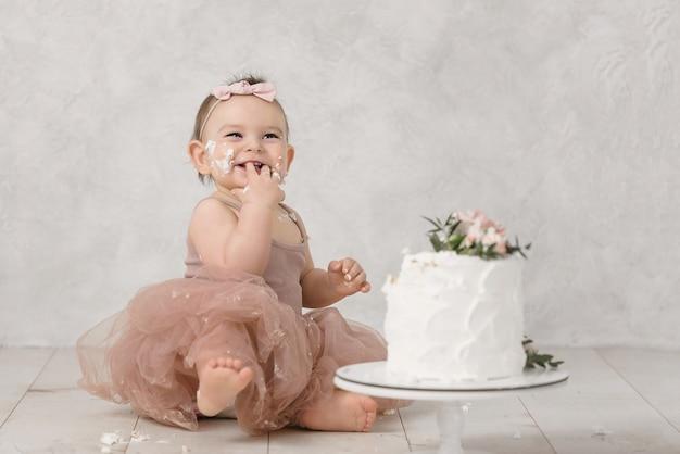 Porträt eines kleinen fröhlichen geburtstagsmädchens mit dem ersten kuchen. den ersten kuchen essen. zerschlagen kuchen