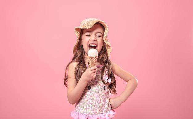 Porträt eines kleinen fröhlichen mädchens in einem sommerhut mit eiscreme in ihren händen, auf einem farbigen rosa hintergrund, sommerkonzept