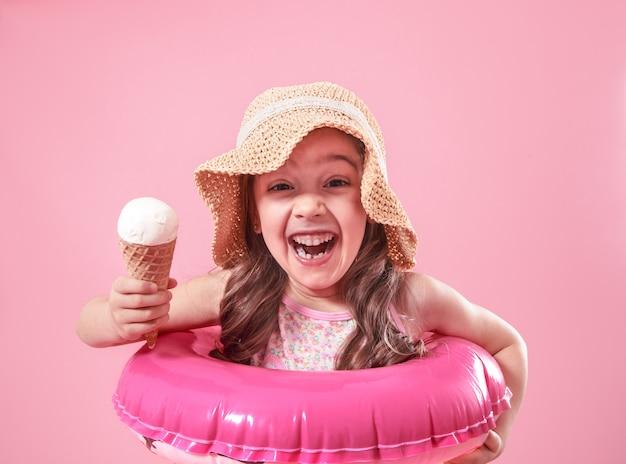 Porträt eines kleinen fröhlichen mädchens mit eis auf einem farbigen