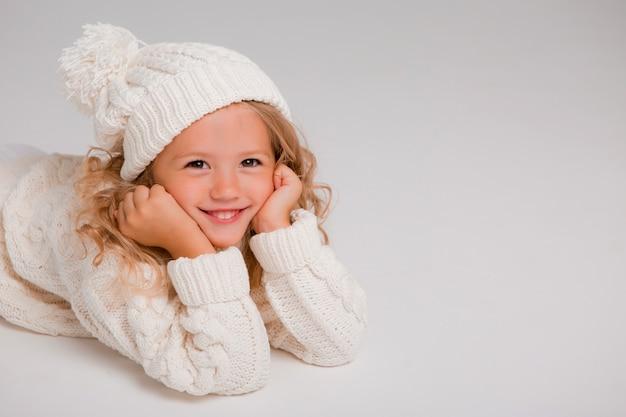 Porträt eines kleinen gelockten mädchens in einem gestrickten weißen winterhut