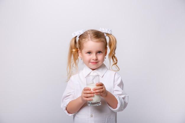 Porträt eines kleinen glücklichen mädchens mit glas milch.