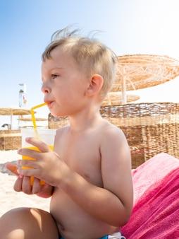 Porträt eines kleinen jungen, der am meeresstrand sitzt und orangensaft aus stroh trinkt. kinder entspannen und haben eine gute zeit während der sommerferien.