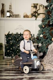 Porträt eines kleinen jungen, der auf einem weinlesespielzeugflugzeug nahe einem weihnachtsbaum sitzt